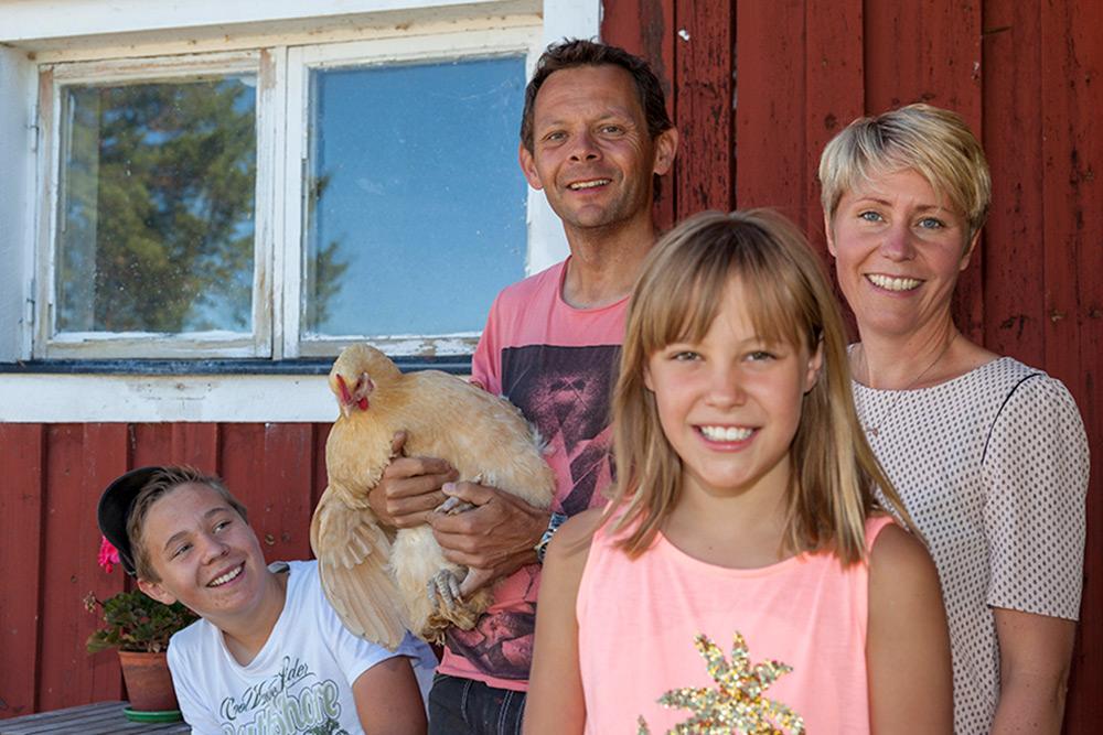 Familj som bor på lantgård, mamma, pappa, pojke och flicka framför en rödmålad vägg. Pappan håller en höna i famnen. Alla ler.