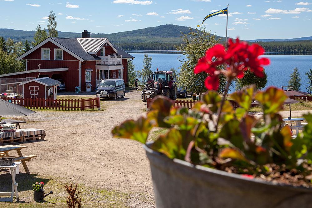 Ett rött hus med vita knutar vid sjö med berg i bakgrunden. På gårdsplanen står en traktor och en bil.