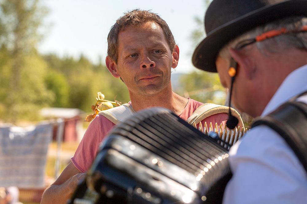 Två män spelar dragspel, den ene tittar på den andre som bär hatt och har ryggen emot.