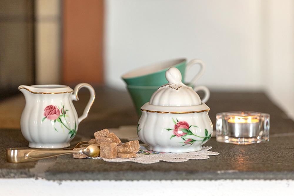 Inredning från café. Sockerskål och gräddkanna i vitt porslin med rosa ros på. Sockertång och två gröna koppar.