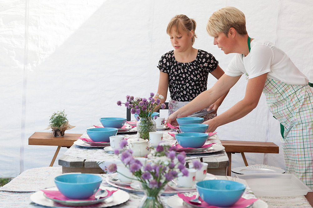Bordet dukas till fest av mamma och dotter. Blommor i vas, blå tallrikar och rosa servetter.