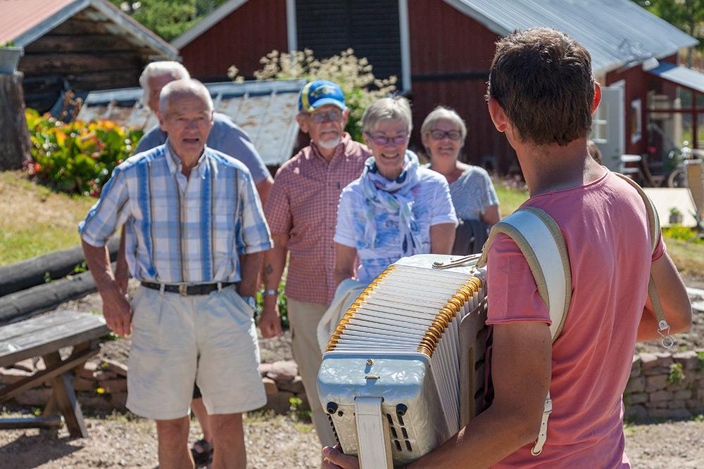 Glada gäster anländer till lantgården och möts av välkomnande man som spelar dragspel