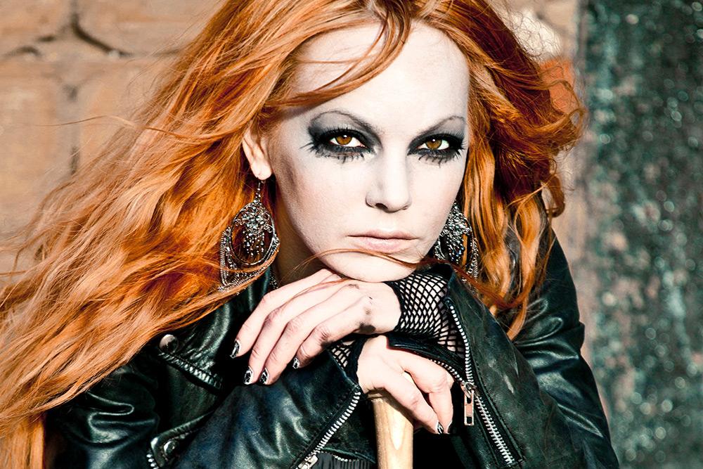 Halvbild på svartklädd kvinna med rött långt hår. Hon har tuff attityd i blicken och är hårt svartsminkad runt ögonen