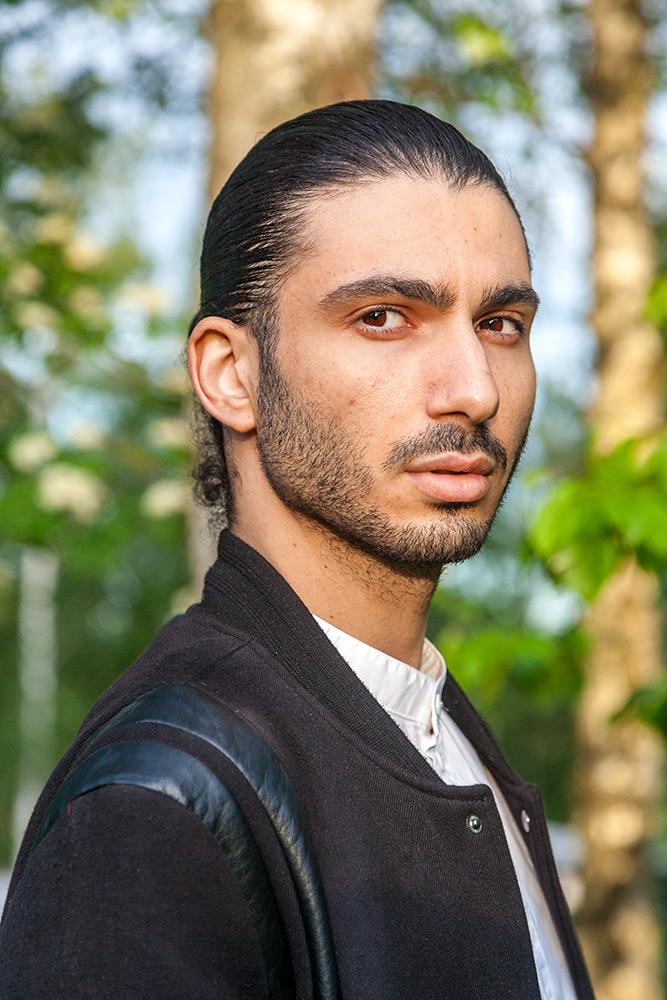 natur i bakgrunden, halvkroppsbild på brunögd ung man med svart jacka har skäggstubb och bakåtslickat svart hår