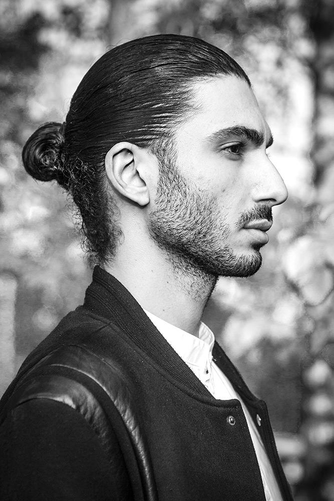 ung man med svart jacka har skäggstubb och bakåtslickat svart hår i profil