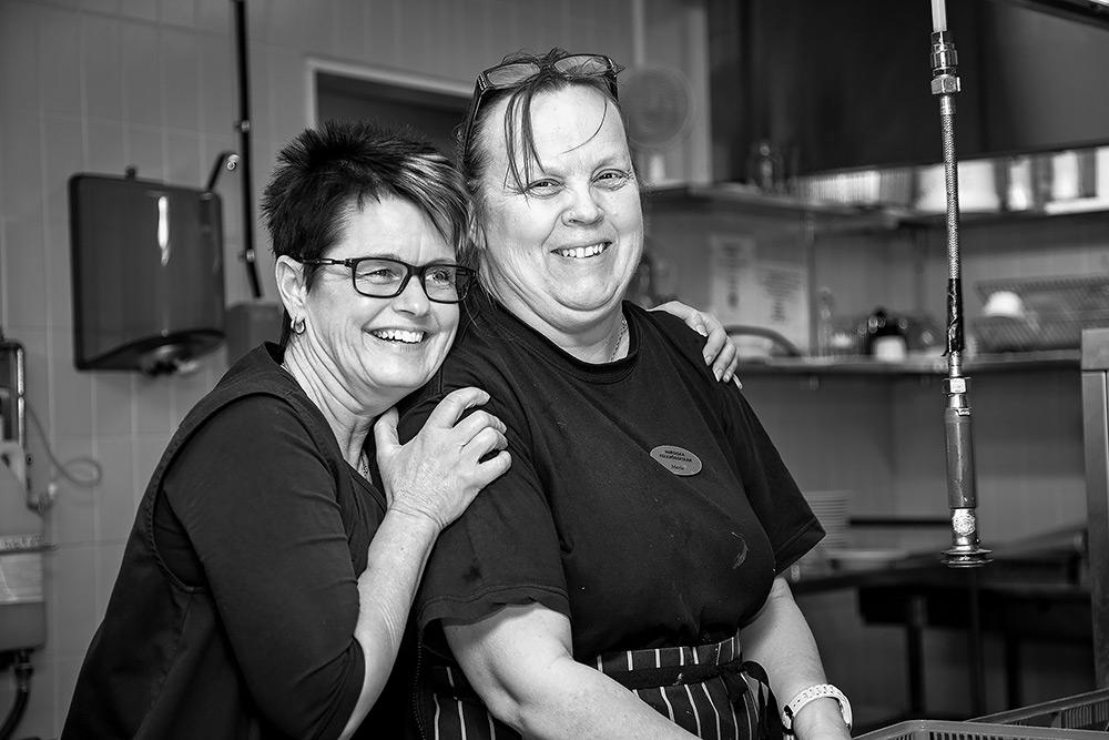 Glad kvinna till vänster med glasögon och mörkt hår håller om glad kvinna till höger som har glasögon uppe i håret. De är arbetskamrater och jobbar i kök.
