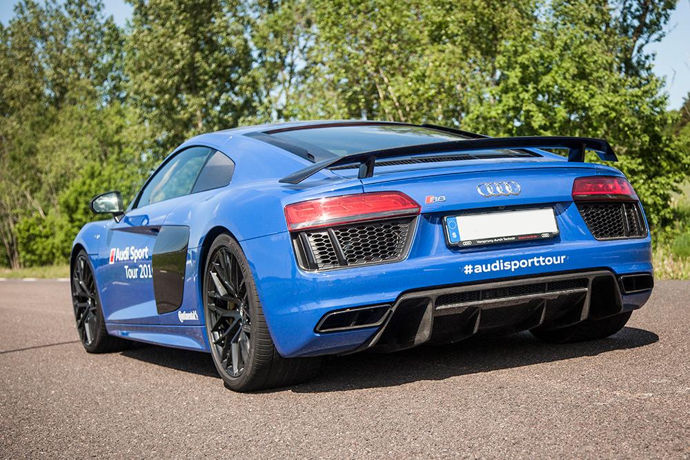 Blå sportbil med vinge bakifrån, Audi R8 på asfalterade väg och gröna träd i bakgrunden