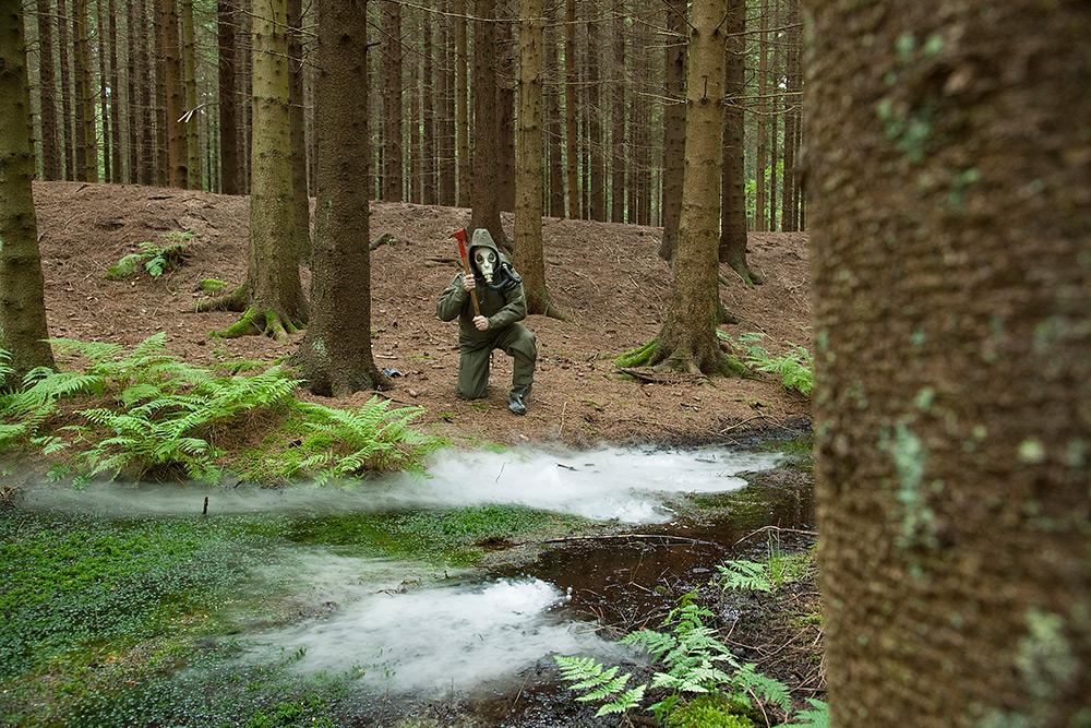 En hotfull man beväpnad med yxa och klädd i grön skyddsdräkt och gasmask vaktar den gamla granskogen. Han står på knä bakom dimma från ett vattendrag.