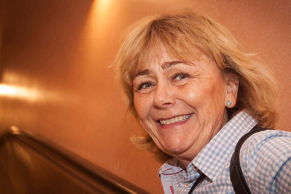 Ansiktsbild på glad äldre riksdagskvinna, moderaten Beatrice Ask i blåvit rutig skjorta