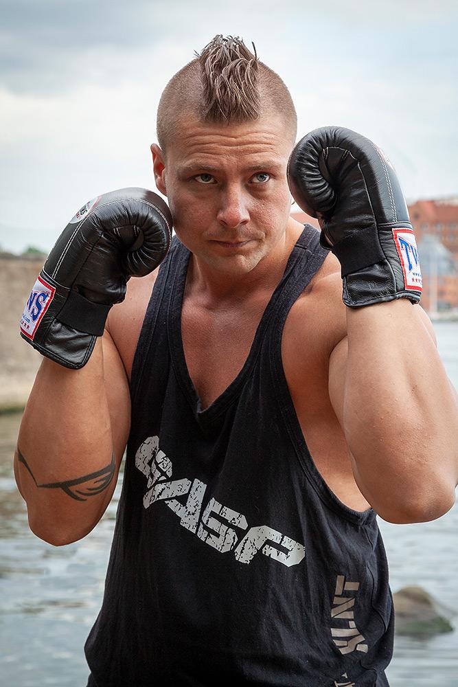 Man med bestämd blick står i försvarsställning med händerna höjda framför sig. Han boxas, bär svart linne och har håret i en tuppkam med rakade sidor.