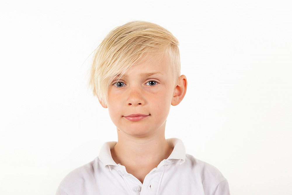 Halvkroppsbild av ljushårig pojke med sidbena och blå ögon i vit tröja