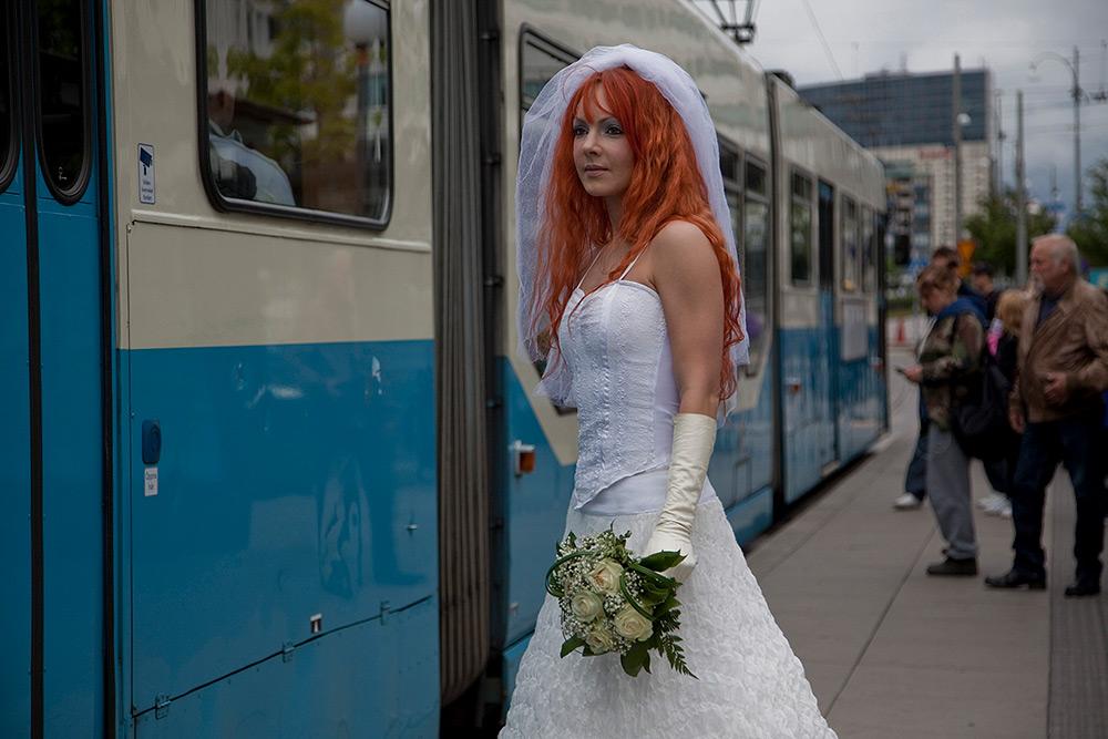 En brud med rött långt hår iklädd bröllopsklänning står utanför en blå spårvagn med en vit bröllopsbukett i sin hand