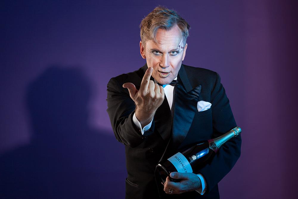 Sminkad man i frack framför lila bakgrund håller en flaska bollinger champagne i famnen och vinkar inbjudande till sig betraktaren med pekfingret