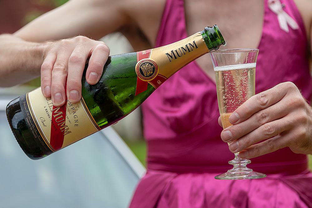 bild på överkropp i rosa klänning, manliga händer håller en flaska champagne och häller upp det i ett glas