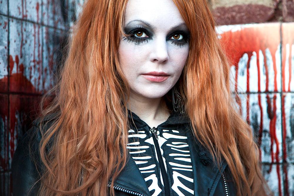 Tuff, svartklädd,rödhårig tjej, svartsminkad runt ögonen står framför en kaklad vägg med stora blodfläckar på.