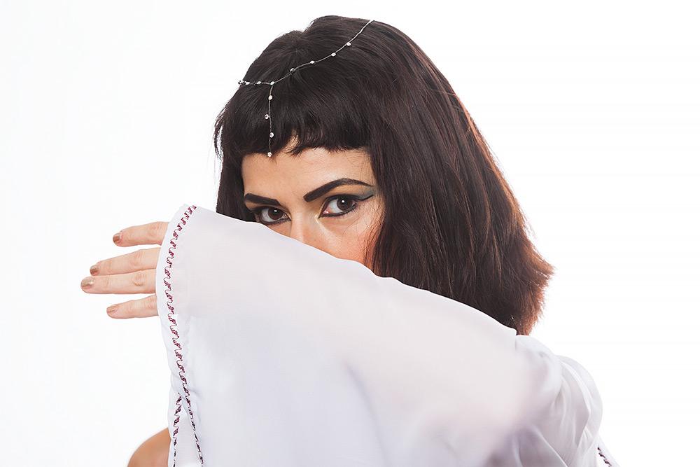 Brunögd välsminkad Cleopatra-liknande kvinna med hårsmycke i sitt bruna hår skyler halva ansiktet med sin vida vita klänningsärm