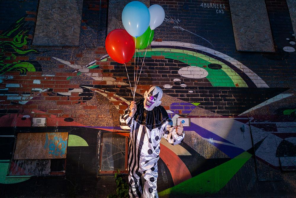 Läskig gubbe i clowndräkt står framför förfallen och nedklottrad byggnad. Han håller en röd, grön, vit och blå ballong i höger hand