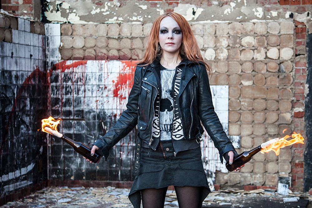 Tuff, svartklädd, tjej med rött långt hår håller två brinnande molotovcocktails i vardera hand. Hon står framför en trasig bränd och blodig tegelvägg.