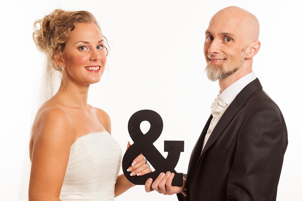 Bröllopspar. Kvinna till vänster med ljust uppsatt hår, blå ögon och rött läppstift i vit klänning. Glad man med rakat huvud och skäggtuss på hakan i svart kavaj. De håller ett och-tecken mellan sig.