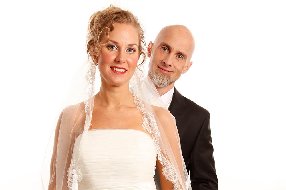 Bröllopspar. Kvinna längst fram med ljust uppsatt hår, blå ögon och rött läppstift i vit klänning. Glad man med rakat huvud och skäggtuss på hakan i svart kavaj står bakom henne.