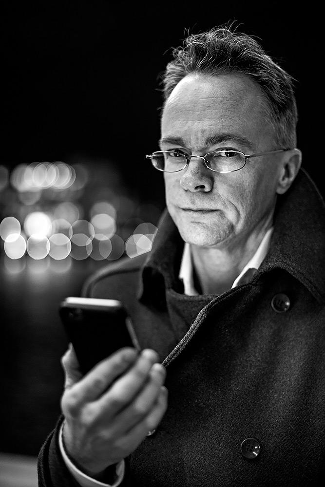 svartvit bild, halvkropp, på medelålders man med glasögon, klädd i rock. han har en mobil i handen som lyser upp hans ansikte