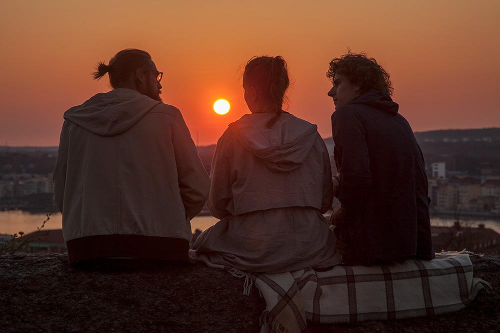 Solnedgång. I bakgrunden syns en blodröd sol. På en mur sitter en ung kvinna med ljol och huvtröja mellan två män som pratar och tittar på varandra. Man till vänster har glasögon, huvtröja och en knut i håret. Man till höger har lockigt halvlångt hår.