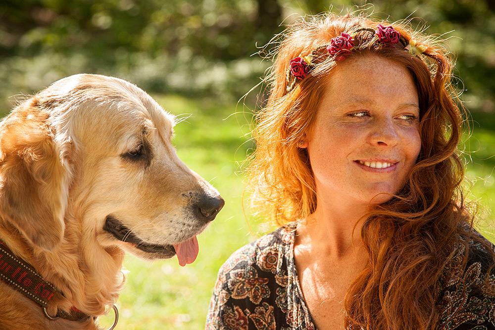 Sommar. Till vänster i profil en gullig golden retriver hund med hängande tunga tittar på en ung kvinna som tittar snett till höger, ler och visar vit tandrad. Hon har hårspännen i det lockiga röda långa håret med röda blommor
