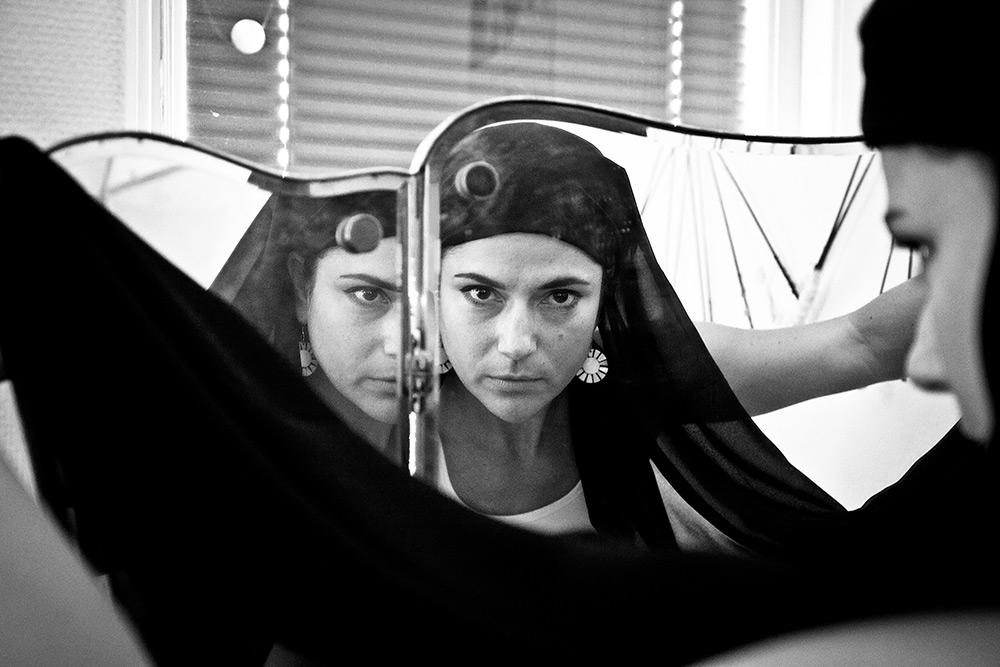 Svartvit bild på kvinna med svart sjal tittar in i spegel, och man ser tre ansikten av henne från olika håll.