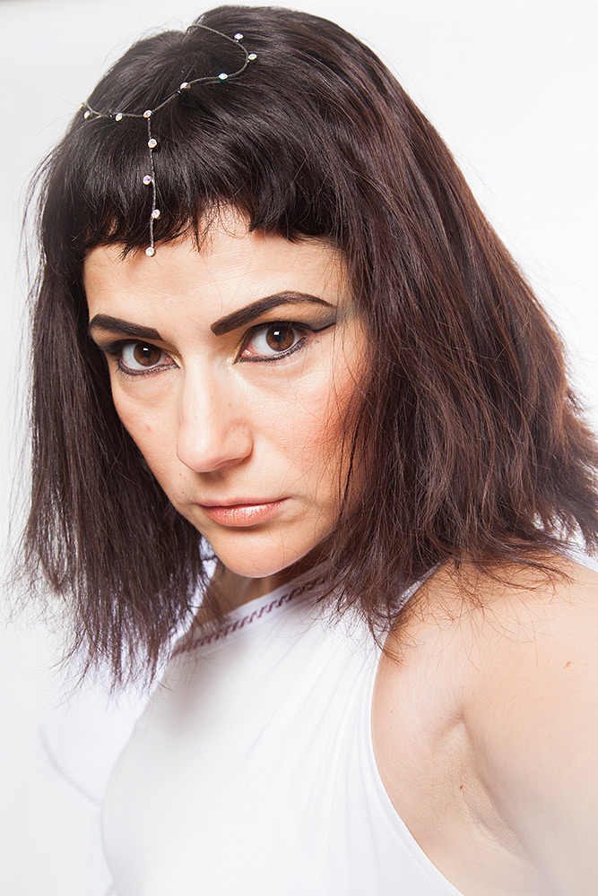 Mörkhårig Cleopatra-liknande kvinna spänner blicken i betraktaren, ger det onda ögat.