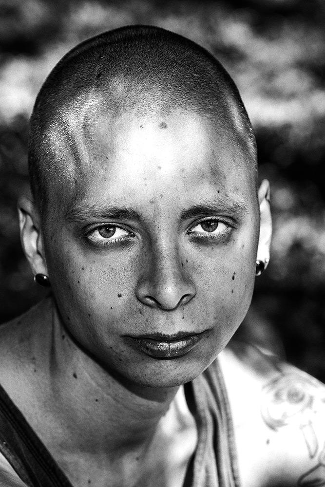 svartvit ansiktsbild av ung man med rakat hår