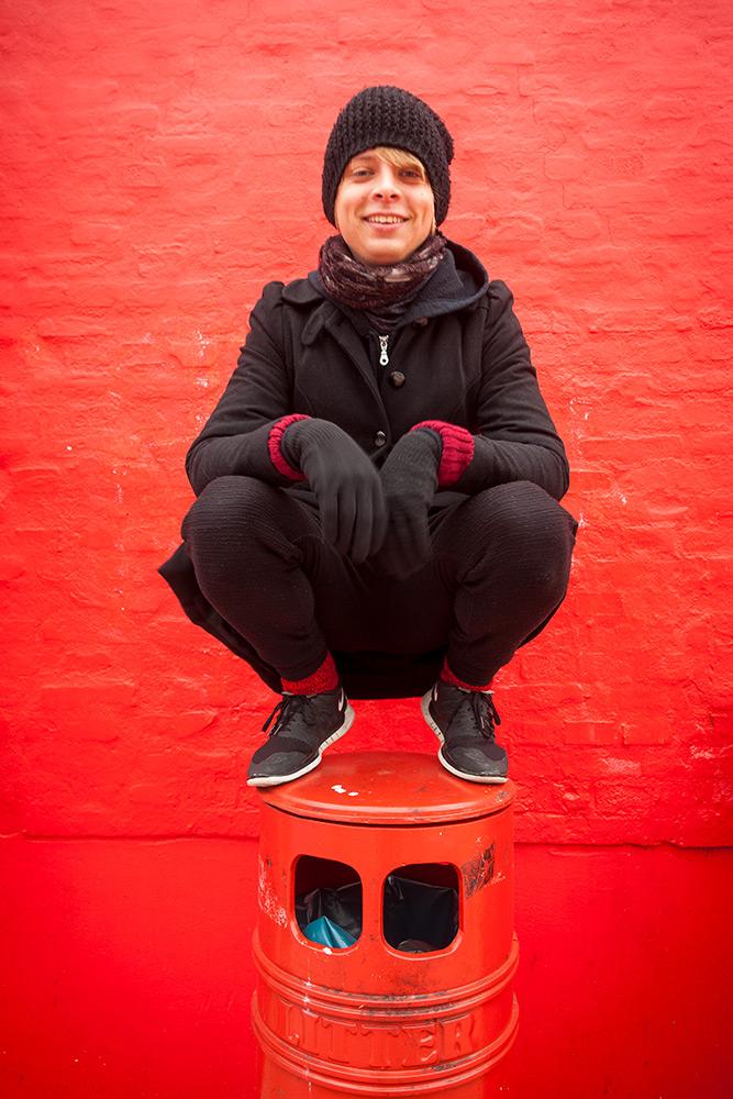 Glad ung man i svarta kläder och stickad svart mössa sitter på huk på en röd papperskorg som står framför en rödmålad vägg.
