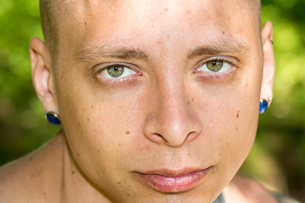 ungansiktsbild av ung man med gröna ögon och piercing i lronen