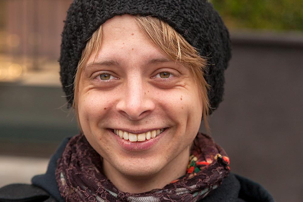 glad ung ljushårig man med skrattgropar bär en svart stickad mössa på huvudet ler stort så tänderna blottas