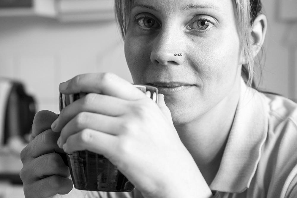 svartvit ansiktsbild på kvinna som håller mugg i handen