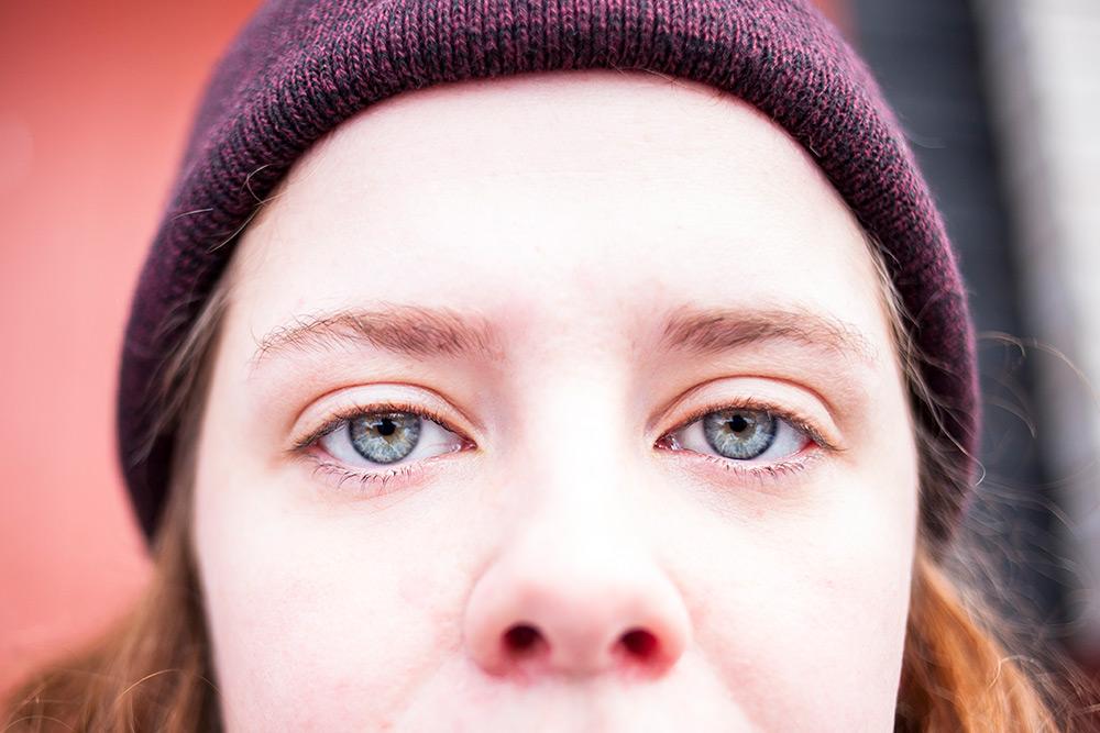 närbild av ung kvinna med lila stickad mössa där man ser näsan lite hår och stora allvarliga blå ögon