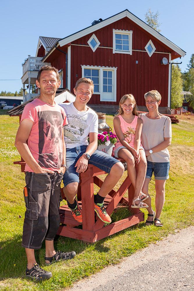 Sommar med grönt gräs på landet. familj, pappa, son dotter och mamma framför rött hus med vita knutar.