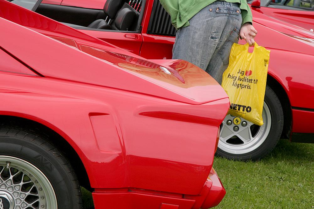 En man står vid en rad röda sportbilar, Ferraris. Han tittar in i en bil och bakom sig har han en gul plastpåse från Netto där det står: Jag älskar hög kvalitet till lågt pris.