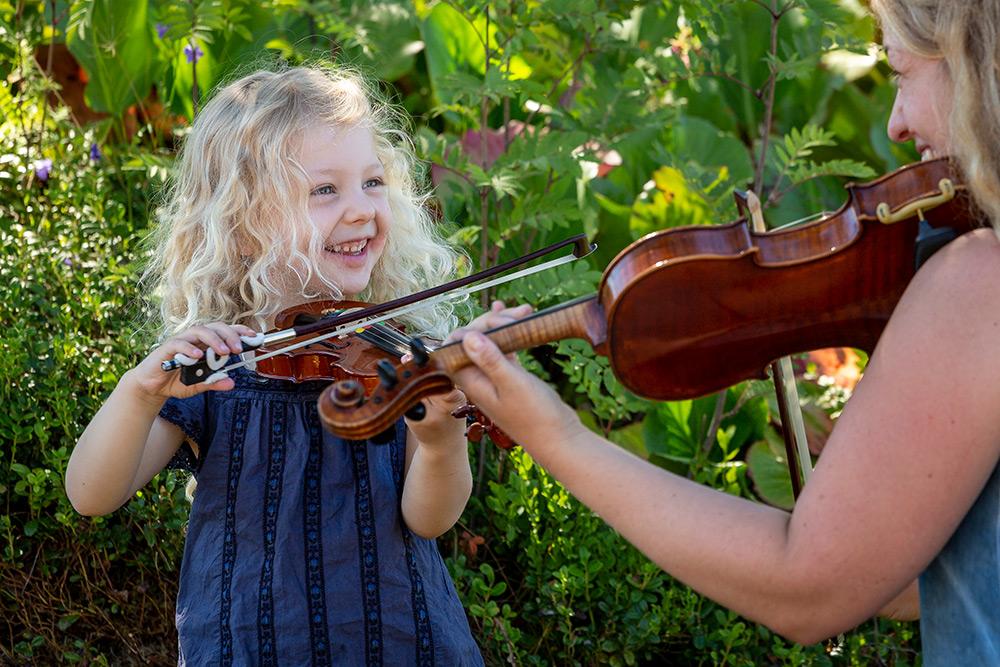 Spelglädje. Liten flicka, dotter, och mor ser leende på varandra och spelar fiol.