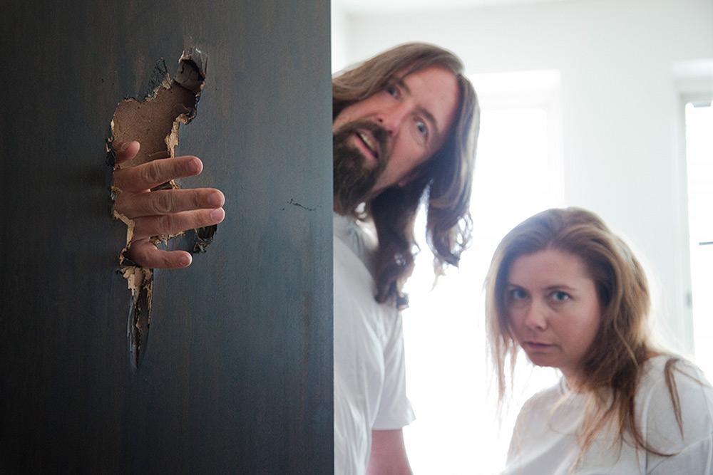 Filminspelning Vitklädda mentalpatienter. Galen man med långt hår och skägg stoppar fingrarna genom en sönderslagen dörr, kvinna i långt hår tittar på.