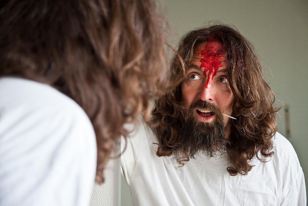 Filminspelning. Mentalpatient, skäggig man med långt hår stirrar på sin spegelbild med gapande mun. Han har blod i pannen.