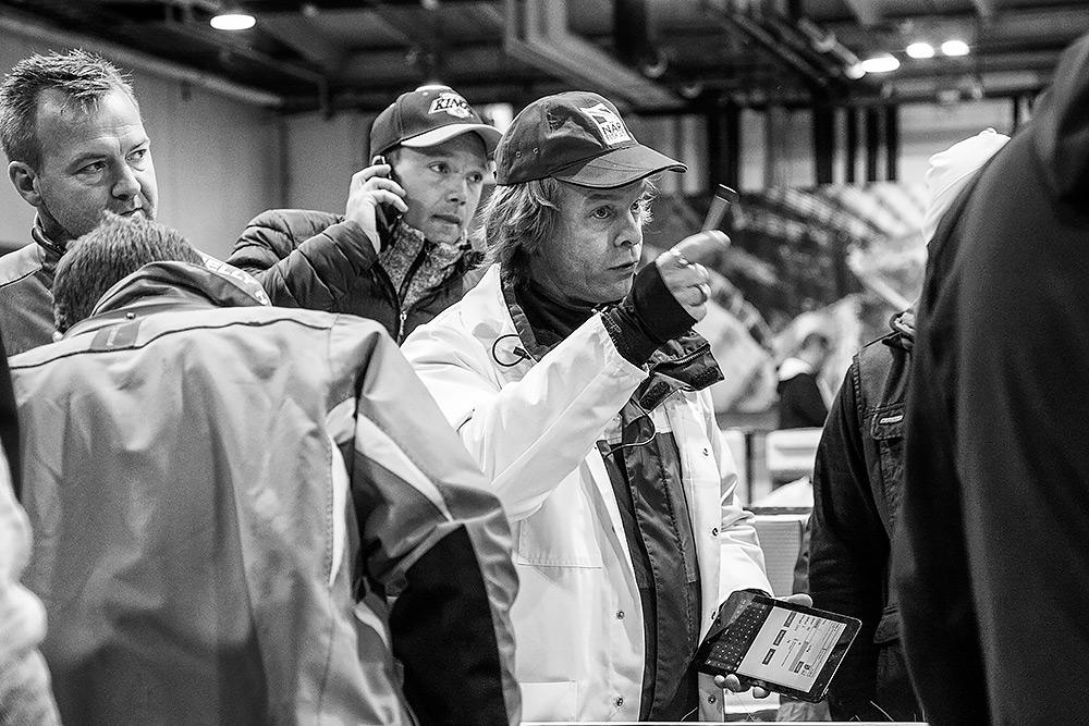 budning fiskauktion, auktionist håller upp pennan, en man talar i telefon bakom honom