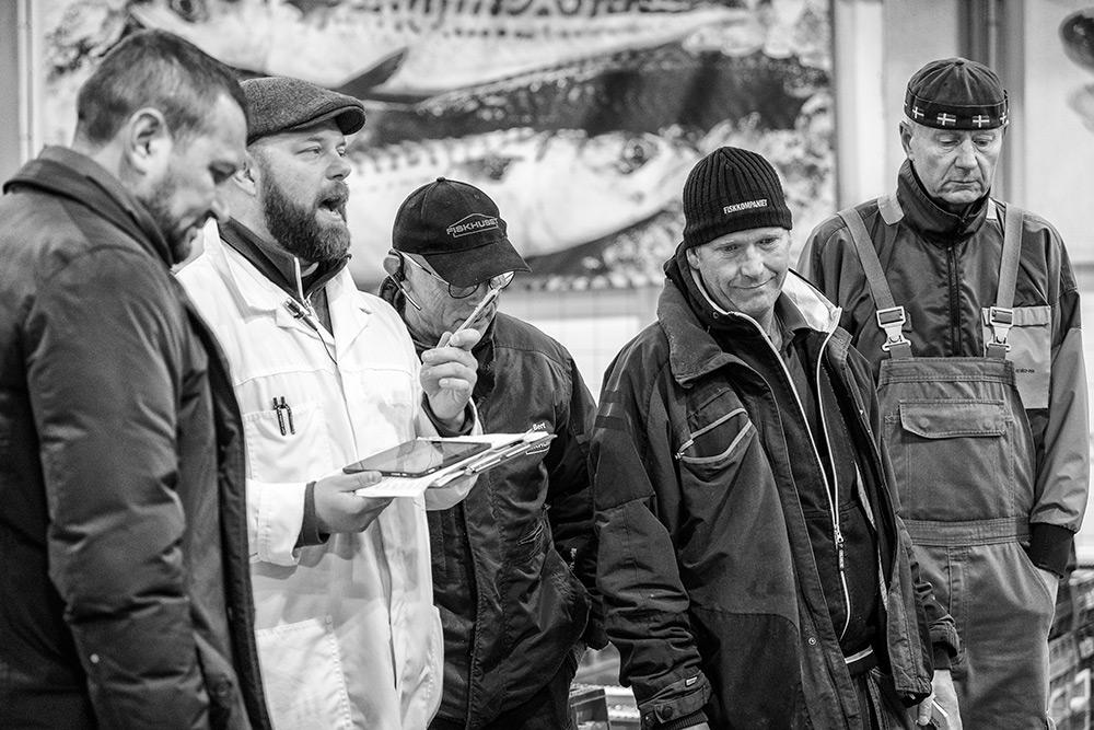fiskauktionisten står omgiven av handlare, alla är män