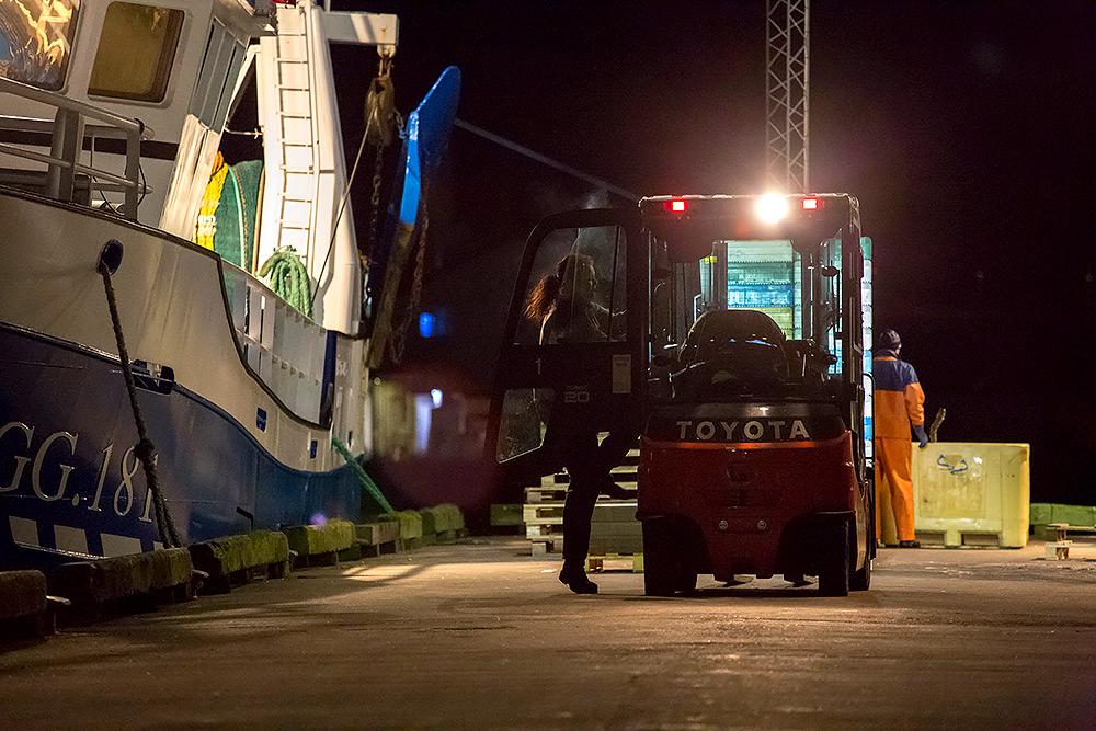 kvinna går in i sin truck utanför fiskebåt som ligger vid kaj i fiskhamnen