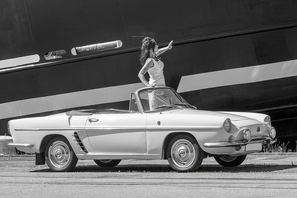 Framför en stor båt i en gammal vit fransk Renault cabriolet står en kvinna i ärmlös klänning med utsträckt hand.