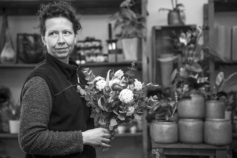 svartvit bild, interiör från blomsteraffär som bakgrund. kvinna med bukett i handen tittar snett bakåt