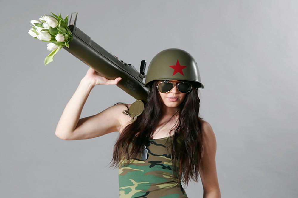 kvinna med pilot solglasögon klädd i grönt kamouflagefärgat linne och en soldathjälm med en röd stjärna på har ett granatgevär på axeln som hon håller i, laddat med vita tulpaner