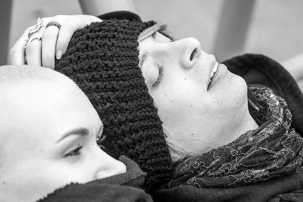 ansiktsbild på hon och han som ligger vid varandras sida. hon har en halsduk upp till näsan, han blundar och har svart stickad stor mössa