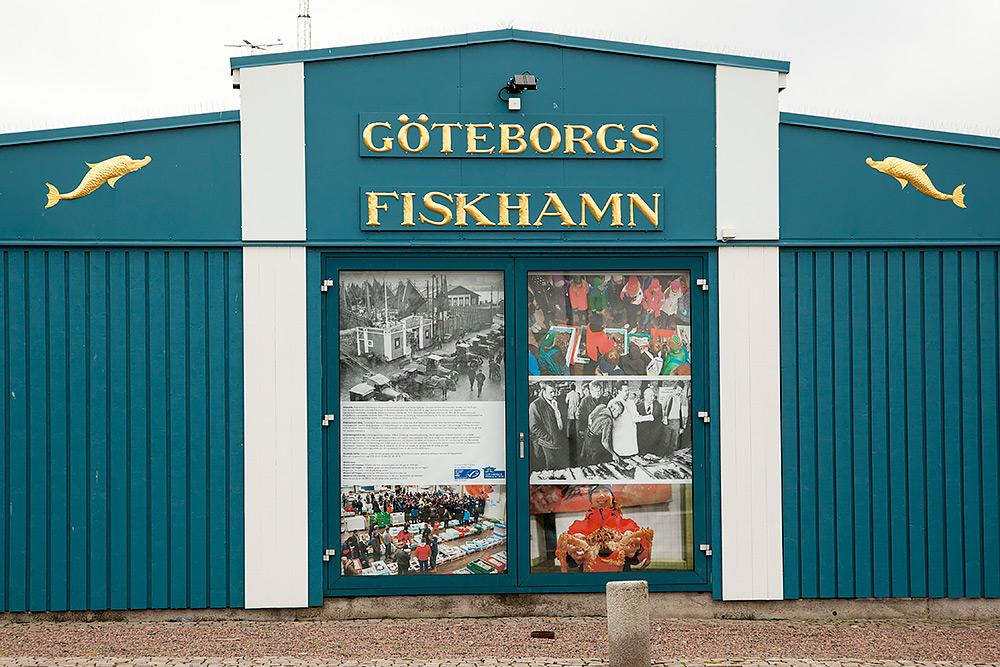 Text: göteborgs fiskauktion, blå fasad med vita stolpar och information på byggnaden