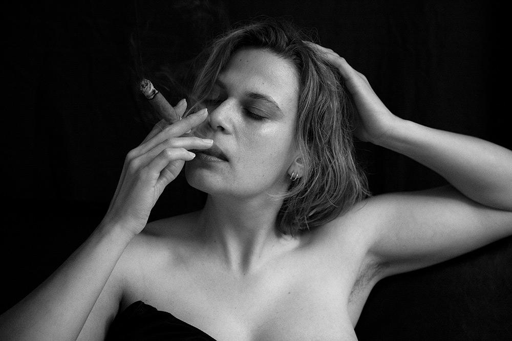 Svartvit bild av kvinna med halvlångt hår som röker cigarr. Hon blundar och tar sig i håret.