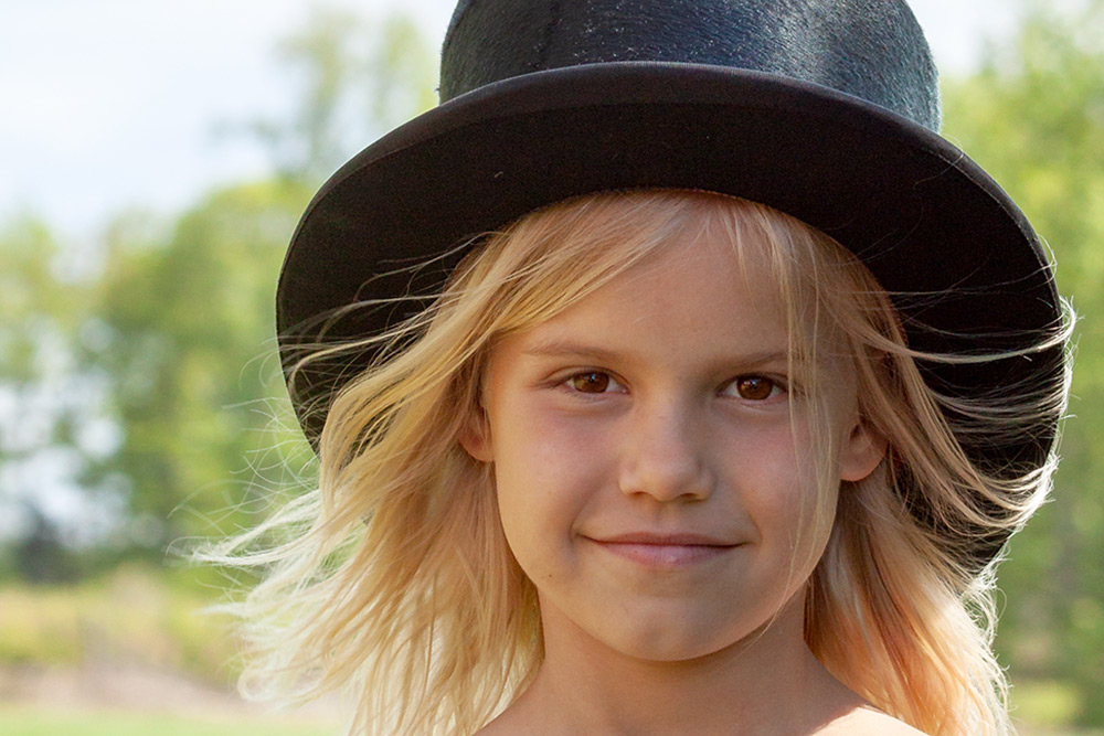 Ansiktsbild av brunögd, Flicka i 7-års åldern med ljust långt hår som vinden leker med, ler och har en stor svart stormhatt på huvudet